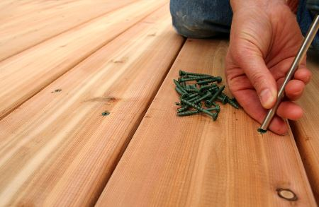 Person putting screws in a deck