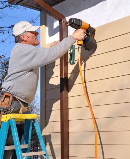 Man applying siding to a house