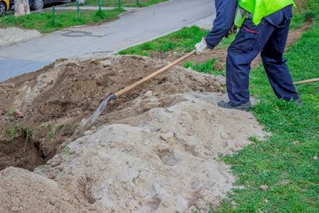 Person digging a hole with a shovel near a sidewalk